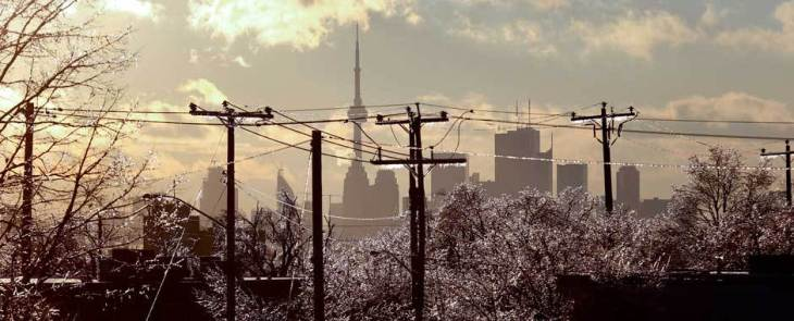 A year ago Toronto was hit by ice storm making it one of the costliest disasters.  Photo: Alex Urosevic for National Post:  Power lines and CN Tower viewed through ice covered branches in Scarborough, December 23, 2013